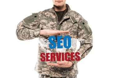 Cropped view man in military uniform gesturing near seo services lettering isolated on white stock vector