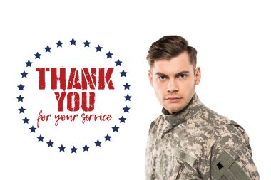 Serious and handsome soldier in uniform looking at camera near thank you for your service lettering on white stock vector