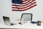 wooden cubes with seo lettering near laptop and american flag in modern office