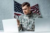 szép katona gazdaság nagyító közelében laptopok
