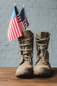 Photo military boots and american flags with stars and stripes on wooden table