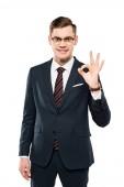 fröhlicher Geschäftsmann in Brille zeigt ok Zeichen isoliert auf weiß