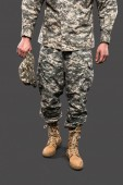cropped view of soldier holding cap and standing isolated on grey