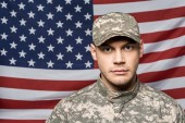 handsome soldier in military uniform and cap looking at camera near flag of america
