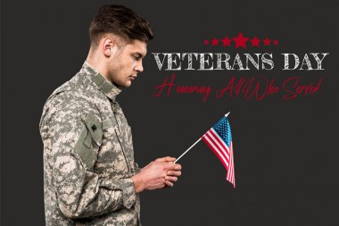 Sad man in military uniform holding american flag near veterans day lettering on grey stock vector