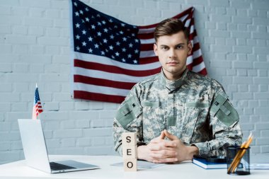Handsome military man sitting with clenched hands near laptop and wooden cubes with seo lettering stock vector