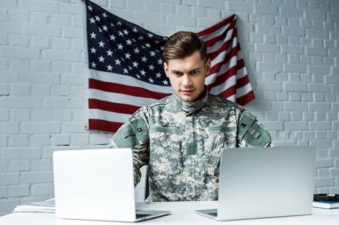 Handsome man in military uniform using laptops in office stock vector