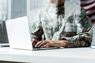 Cropped view of soldier in camouflage uniform using laptop stock vector