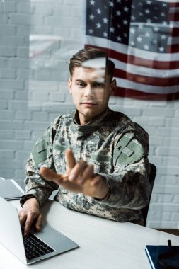 Selective focus of handsome man in camouflage uniform pointing with finger in office stock vector