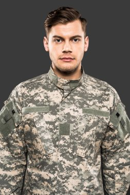 Serious soldier in uniform looking at camera isolated on grey stock vector