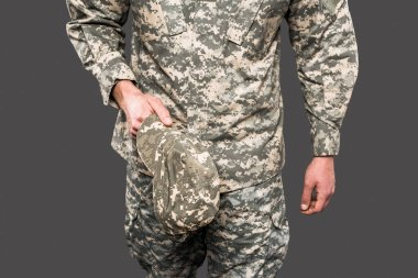 cropped view of soldier holding cap isolated on grey