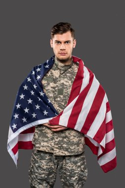 handsome man in military uniform with american flag isolated on grey
