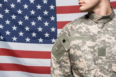 Cropped view of man in military uniform near flag of america stock vector