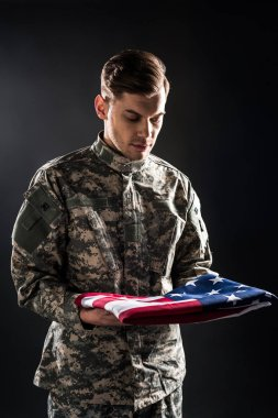Man in military uniform looking at american flag on black stock vector