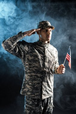 confident soldier in military uniform holding american flag and giving salute on black with smoke