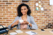 Fotografie smiling african american Casual businesswoman at desk with coffee cup in office