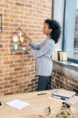 Casual african american businesswoman hanging Sticky Notes with pins in loft office