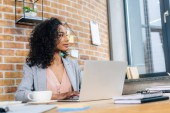 Photo african american Casual businesswoman sitting at office desk with laptop