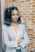 african american Casual businesswoman with crossed arms looking through window in loft office