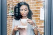 afroamerická příležitostná obchodní žena s kávovou šálnou za oknem