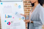 oříznutý pohled na afroameričanky příležitostná obchodní žena s grafem blízko flipchart v podkrovní kanceláři