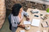 Alkalmi afrikai amerikai üzletasszony ülő-on iskolapad és írás-ban jegyzetfüzet-ban padlásszoba Hivatal