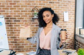 Fotografie african american Casual businesswoman holding takeaway paper bag and coffee to go in office