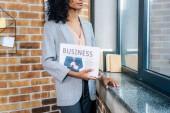 Oříznutý pohled na Africkou americkou příležitostnou Obchodni s obchodním novinám v podkrovní kanceláři