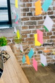 selective focus of colorful Sticky Notes on glass window in loft office