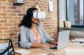 afroamerická příležitostná obchodní žena ve virtuální realitě sluchátka s kancelářskou kanceláří pomocí přenosného počítače