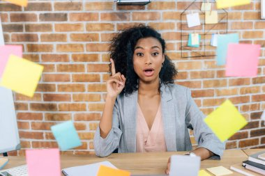 surprised african american Casual businesswoman sitting at desk and doing idea gesture in front of glass window with Sticky Notes