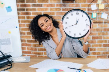smiling african american Casual businesswoman holding clock in loft office