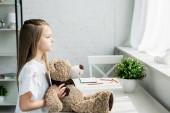 roztomilý kluk s medvídkem, který stojí u stolu doma