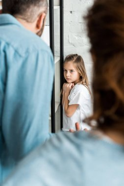 selective focus of frustrated kid looking at father at home