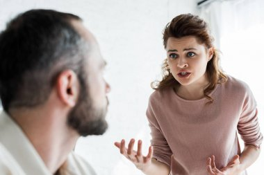 selective focus of offended woman gesturing while looking at man