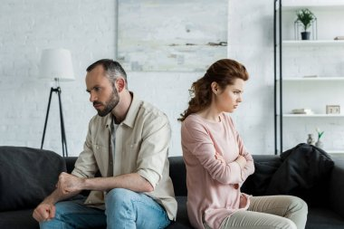 upset woman sitting near angry husband with crossed arms at home