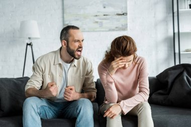 angry man sitting on sofa and screaming at upset woman