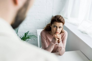 selective focus of upset woman with clenched hands looking at man