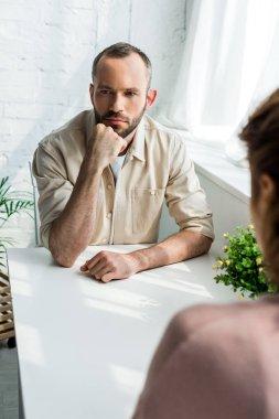 selective focus of sad man sitting near woman at home