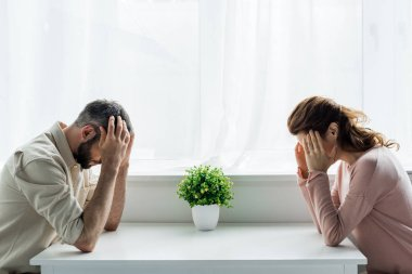 upset man and woman sitting at home after quarrel