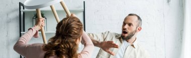 panoramic shot of surprised man looking at angry holding chair while threatening at home