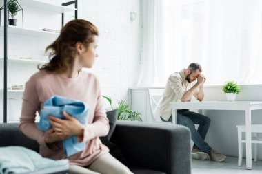 selective focus of frustrated man sitting on chair near table and upset woman with clothes in hands