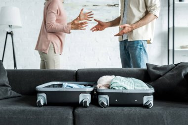 Cropped view of man and woman standing and gesturing near suitcase with clothes on sofa stock vector