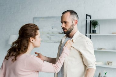 angry woman touching shirt of handsome bearded man at home