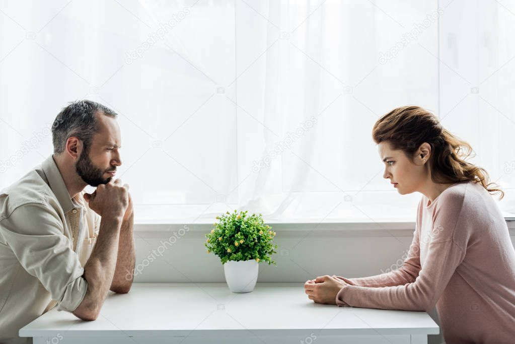 Handsome bearded man and upset and attractive woman after quarreling at home