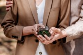 Cropped view of stylish couple holding box with wedding ring