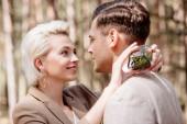 Lächelndes blondes Mädchen hält Box mit Eheringen und umarmt Bräutigam im Wald