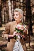 elegáns szőke nő fülbevalóval gazdaság csokor és elnéz az erdőben