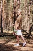 teljes hosszúságú kilátás a stílusos menyasszony gazdaság esküvői csokor erdőben