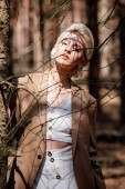 Photo stylish blonde young woman standing in forest and looking at camera